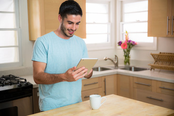 Man with smart tablet device reading the morning news with a  cup of coffee at home single male