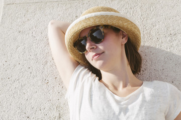 young casual girl wearing a hat and sunglasses relaxed