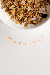 Vertical Morning text stamped under bowl of fresh cereal and mil