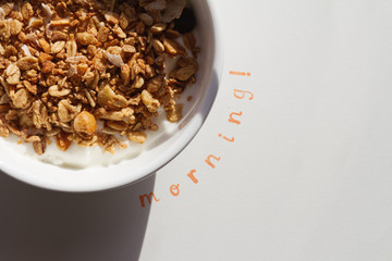The word Morning stamped next to a bowl of muesli and yogurt