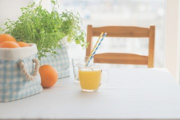 Fresh orange juice for breakfast. Breakfast table scenery with fresh orange juice and blue basket filled up with oranges.