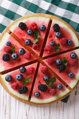 Watermelon decorated with berries close-up vertical top view
