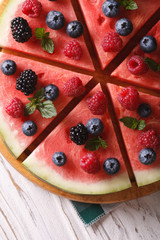 Sliced watermelon with berries and mint close-up. Vertical top view