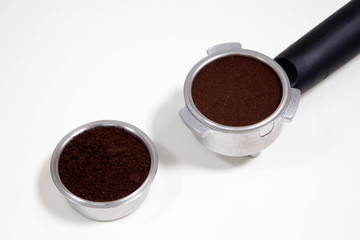 Portafilter filled with ground coffee on a white background