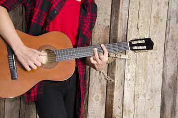 young man no face, playing guitar in plaid shirt next to wooden barn door
