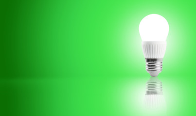 Glowing LED energy saving bulb on a green background.