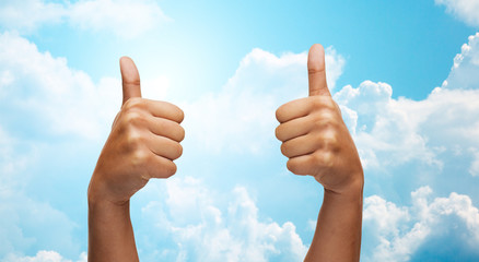 african hands showing thumbs up over blue sky