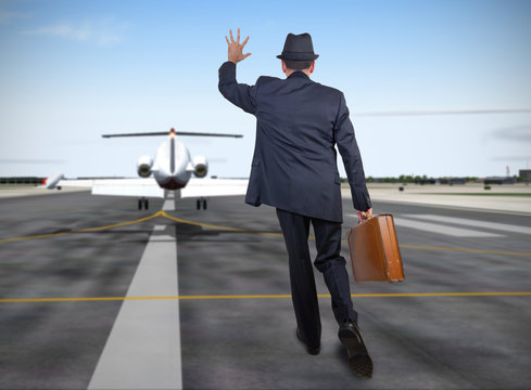 Business man running behind a plane