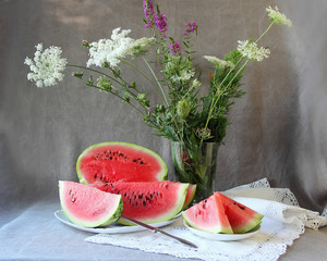 Still life with wild flowers and ripe watermelon..