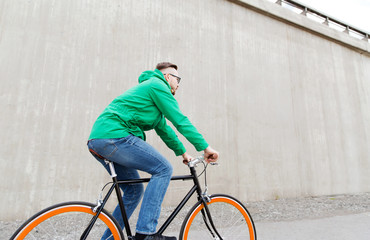 happy young hipster man riding fixed gear bike