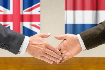 Vertreter Großbritanniens und der Niederlande reichen sich die