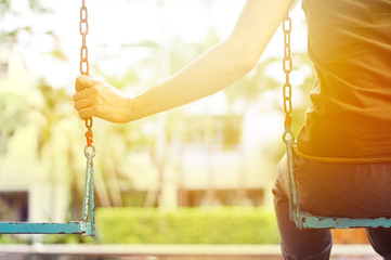 Lonely woman missing her boyfriend while swinging in the park of villa