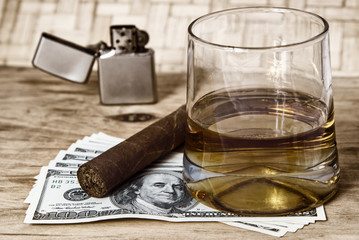Glass of whiskey and a money with cuban cigar and lighter on a wooden table.