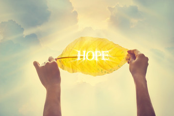 Vintage color tone, holding a yellow leaf in the sky of hope Wall mural