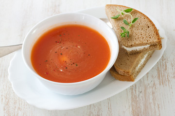 tomato soup in white bowl with sandwich on white background