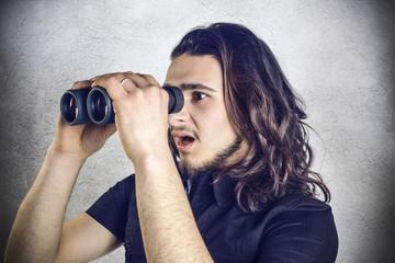 Astonished young man using a binocular