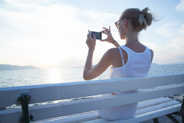 Blonde woman using cellphone on vacation.
