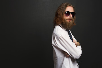Close up stylish gorgeous young  businessman with long beard with glasses on black background