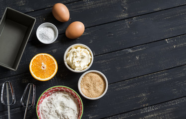 raw ingredients - flour, eggs, butter, sugar, orange - to cook orange cake. Ingredients for baking. Ingredients for the dough. On a dark wooden surface