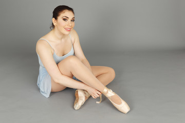 A seated ballerina smiling at viewer.