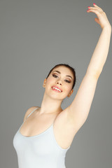 A ballerina smiles at viewer with her arm up.