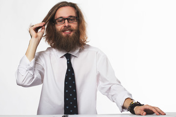 Handsome young businessman with beard and glasses thinking at the table on white background
