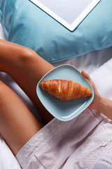 Woman eating a croissant in the bed