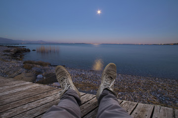 View of the moon reflected in the lake at night with legs and feet in first