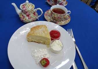 British-style afternoon tea with scone, butter, cream and strawberry jam.