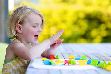 Little girl playing with plasticine and colorful forms. Happy child, adorable toddler girl creating from modeling compound dough, sitting outdoors in the garden on sunny summer day