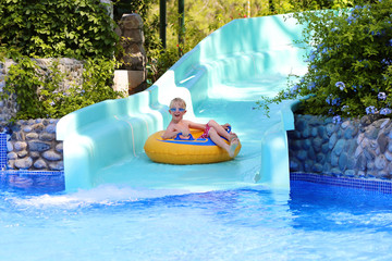 Happy kid, blonde caucasian boy, having fun floating and sliding in water park on inflatable ring enjoying sunny summer vacations in tropical resort