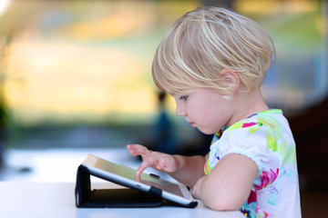 Happy little child, adorable blonde toddler girl enjoying modern generation technologies playing indoors using tablet pc with touchscreen