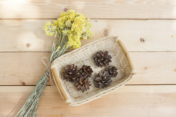 Dwarf everlast flowers bouquet and pine cones in a wicker basket on light wooden table, selective focus