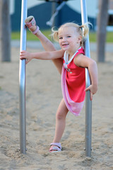 Happy kid enjoying active summer vacation. Sportive funny little child, blond cute toddler girl, having fun outdoors climbing on playground in the park on a sunny day