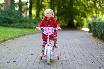 Little child riding her bicycle in the park. Cute preschooler girl learning to cycle with stabilisers wheels. Sportive kid enjoying sunny autumn day outdoors.