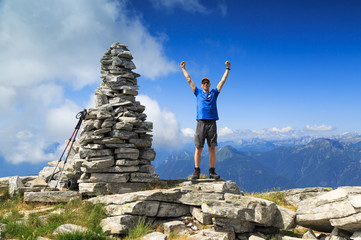 Man raising his hands out of joy on a mountaintop.