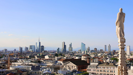Panoramic view of Milan skyline from Duomo cathedral. Religious statue faces to the buildings of the financial district. The Alps mountains on the background.