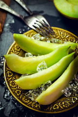 Fresh sweet melon with ice on a plate