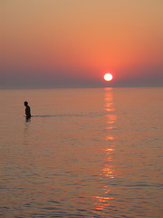 Man in the sea at sunrise