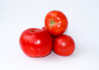 Three tomatoes on a white background.