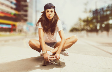 Girl sitting on a Skateboard in the City