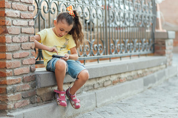 little girl is sitting outdoor and playing on the phone