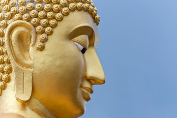 Golden Buddha head. Buddha statue on blue sky background.