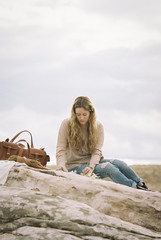 Woman sitting on a rock a leather bag beside her.