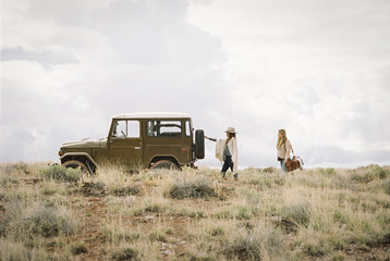 Two women by a jeep in open space, loading up for a road trip.