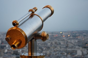Vintage Telescope looking over city at dusk