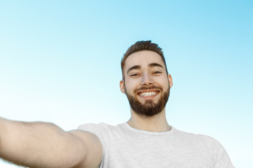 Young man taking selfie in park