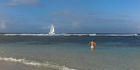 Man and Boat on tropical sea under blue sky