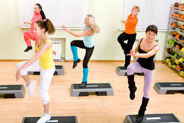 Women Different Nationalities Doing Step Aerobics in the Gym