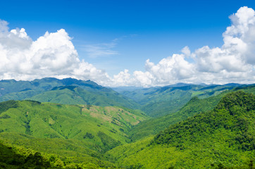 green mountains and blue sky with clouds